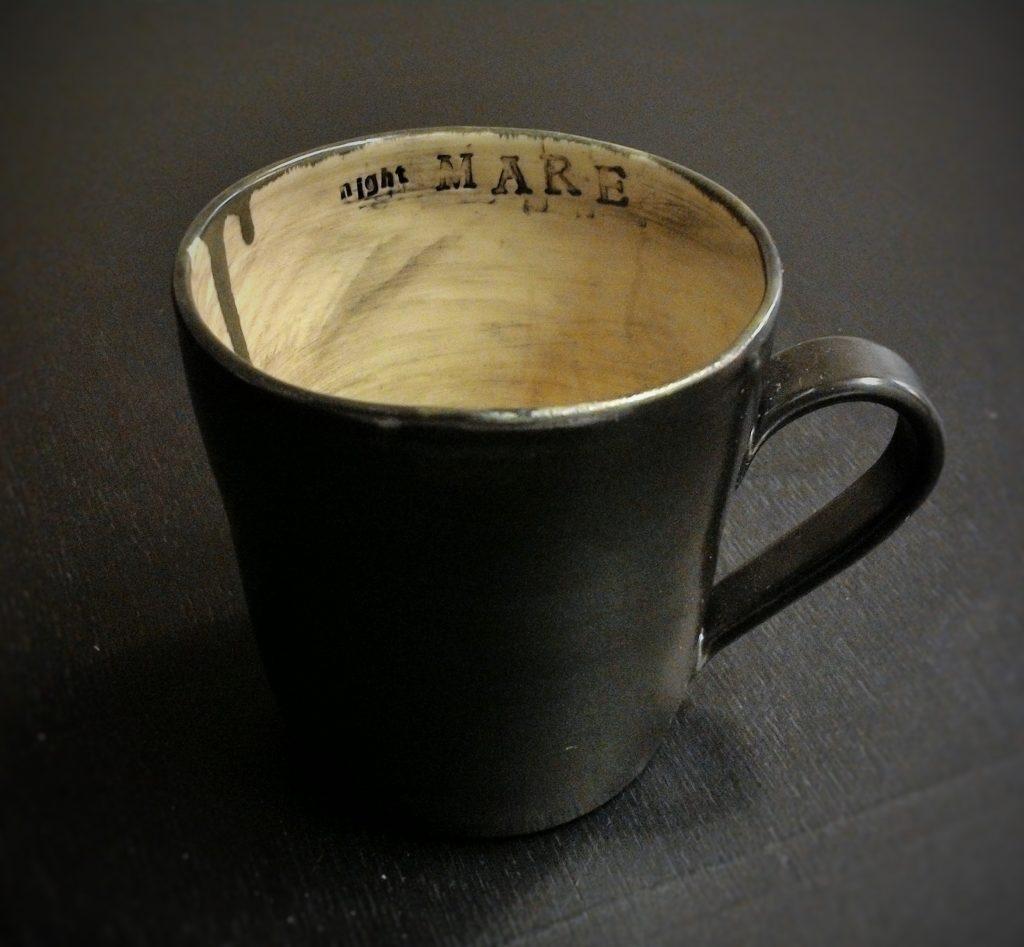 Musta keraaminen muki, jossa vaaleaan sisäpintaan stanssattu teksti nightMARE.