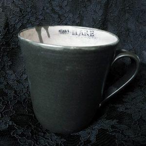 Käsin tehty musta keraaminen muki, jossa stanssattu teksti nightMARE