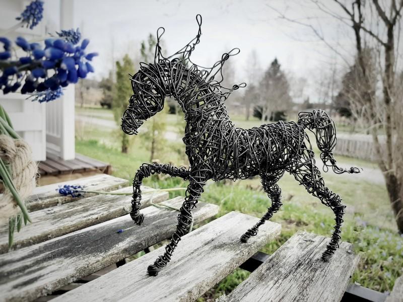 Tummasta rautalangasta tehty laukkaava hevonen