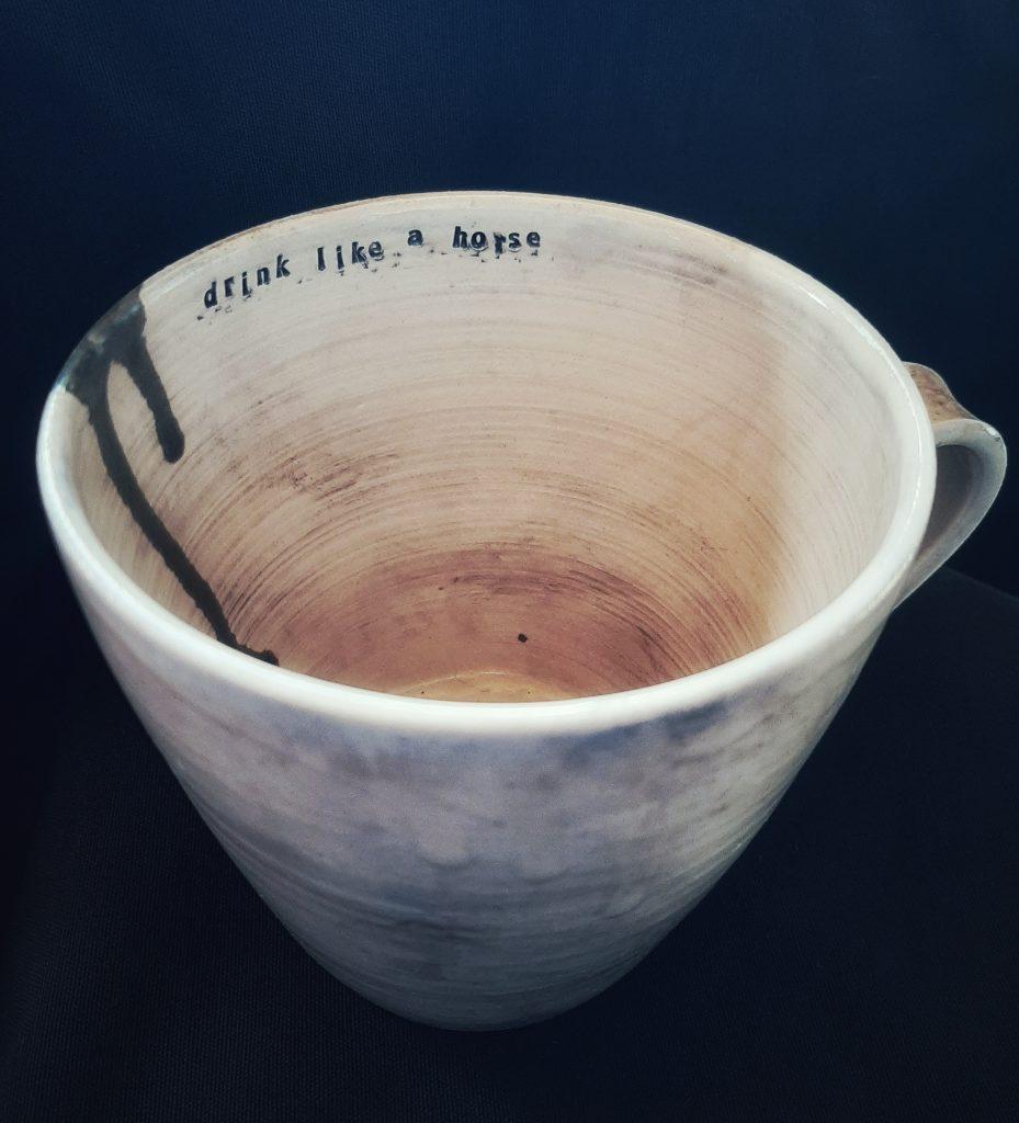 Käsin tehty vaalea muki jossa teksti drink like a horse
